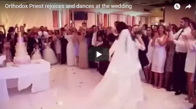 Orthodox Priest rejoices and dances at the wedding